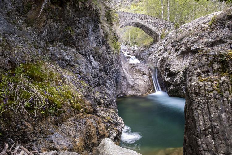 Arch bridge over water flowing through rocks
