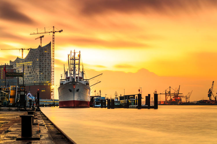 Ships moored at commercial dock against sky during sunset