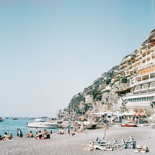Just got back from Europe and had 8 rolls of film developed- here's a shot from a beach in Positano🇮🇹 Large Group Of People Sea Copy Space Clear Sky Real People Beach Day Outdoors Vacations Nature Water Travel Destinations Architecture Building Exterior Built Structure Lifestyles Men Women Scenics Sky Film Photography Analogue Photography Tranquil Scene Landscape_photography Mountains