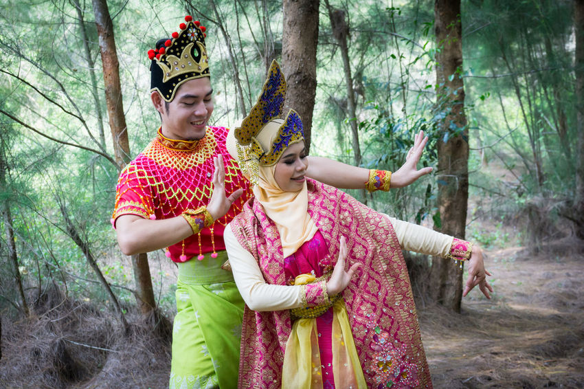 Specific to the villages of Kelantan, where the tradition originated, Mak Yong is performed mainly as entertainment or ritual purposes by couple of dancers. Casual Clothing Childhood Crown Day Forest Front View Girls Headdress Headwear Leisure Activity Mak Yong Nature Outdoors People Playing Real People Smiling Standing Togetherness Tree Tree Trunk