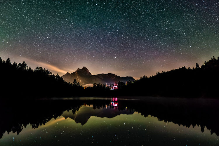 Night sky reflection in lake urisee with alps mountains in background