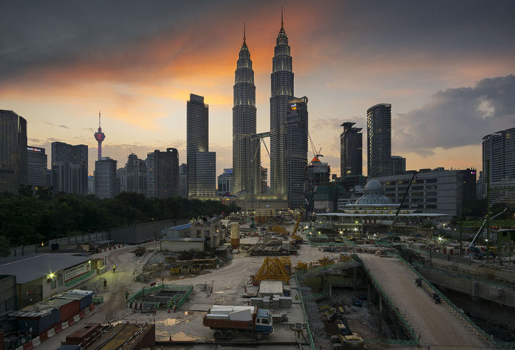 Petronas towers with cityscape against sky during sunset