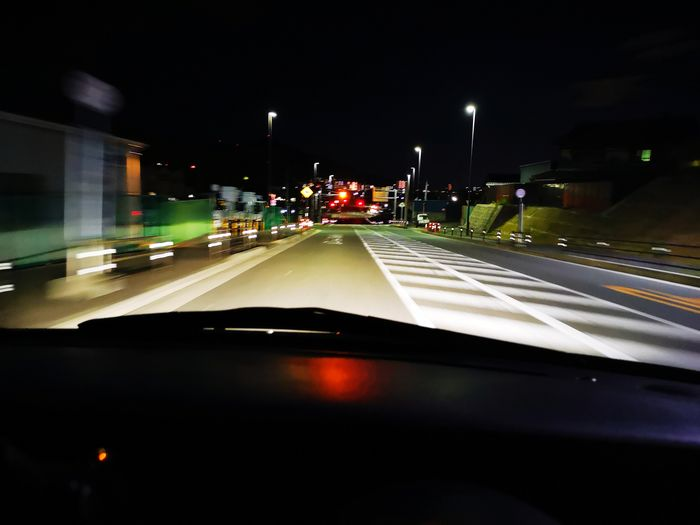 Cars on road seen from car windshield at night