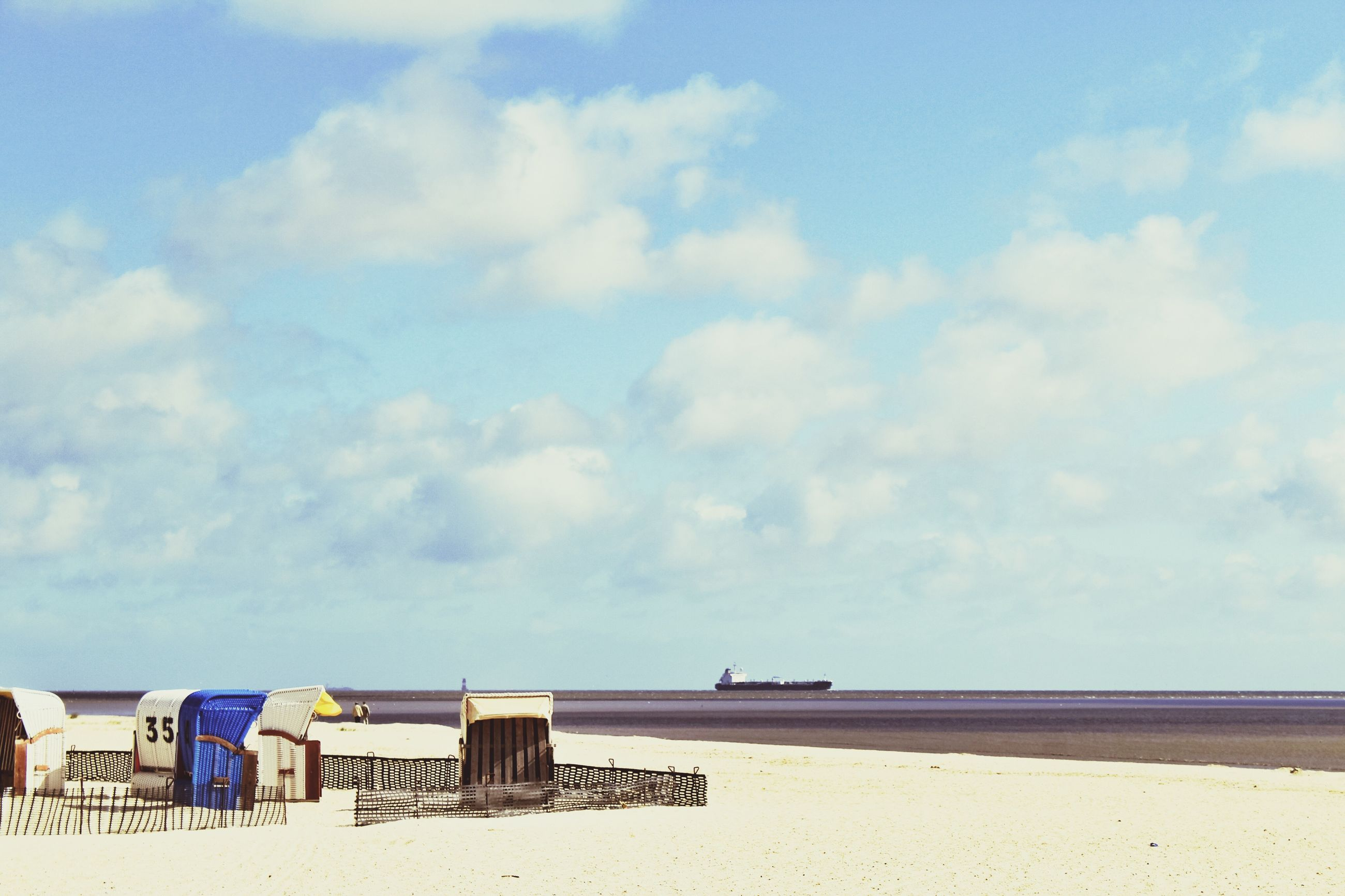 sea, beach, sky, water, horizon over water, sand, shore, tranquility, tranquil scene, scenics, beauty in nature, nature, cloud - sky, blue, cloud, day, built structure, outdoors, idyllic, calm