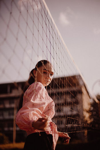 Side view portrait of young woman standing by volleyball net against blue sky
