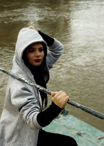 Young woman holding metal against lake