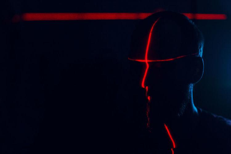 Laser light falling on man in darkroom