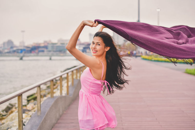 Architecture Arms Raised Beautiful Woman Beauty Casual Clothing Clothing Day Fashion Focus On Foreground Hair Hairstyle Human Arm Leisure Activity Lifestyles One Person Outdoors Pink Color Portrait Real People Smiling Standing Women Young Adult Young Women