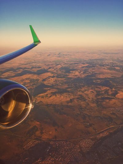 Aerial View Of Airplane Wing Over Landscape Against Sky