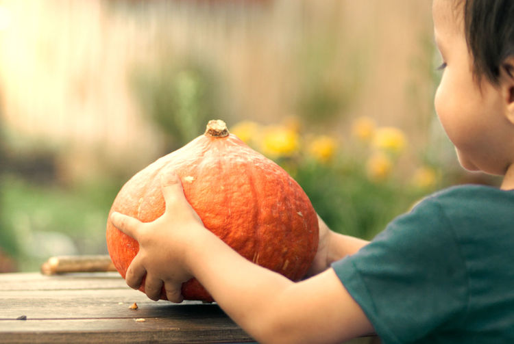 Midsection of man holding pumpkin against blurred background