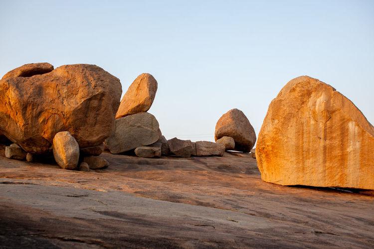 Rocks on desert against clear sky