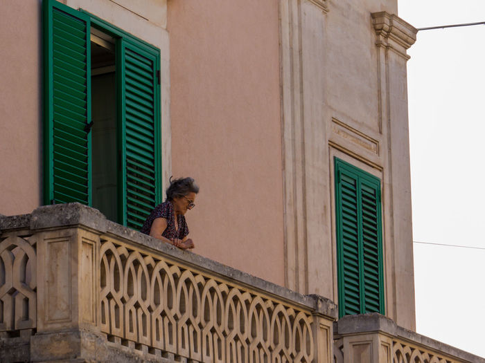 Side view of woman walking on balcony of building