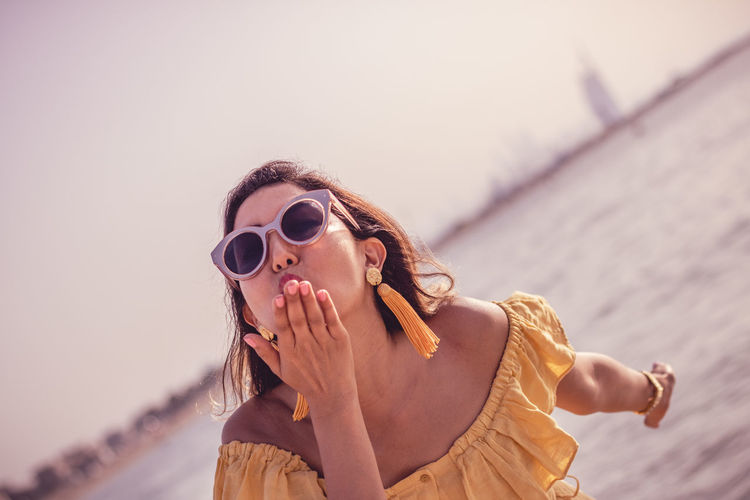 Woman Blowing Kiss While Standing At Beach