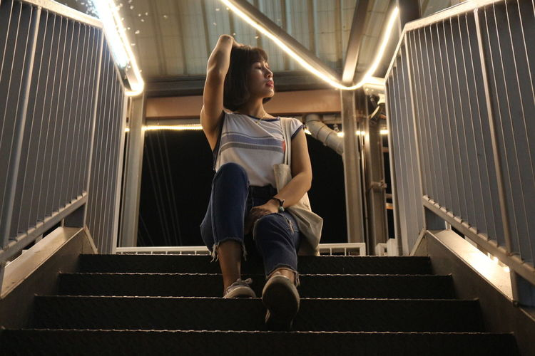 Low angle view of woman sitting on staircase at night