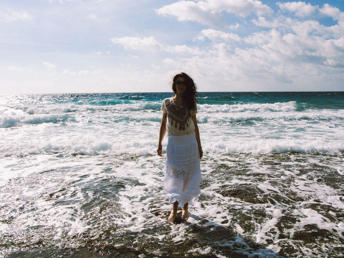 Woman wading in sea against sky