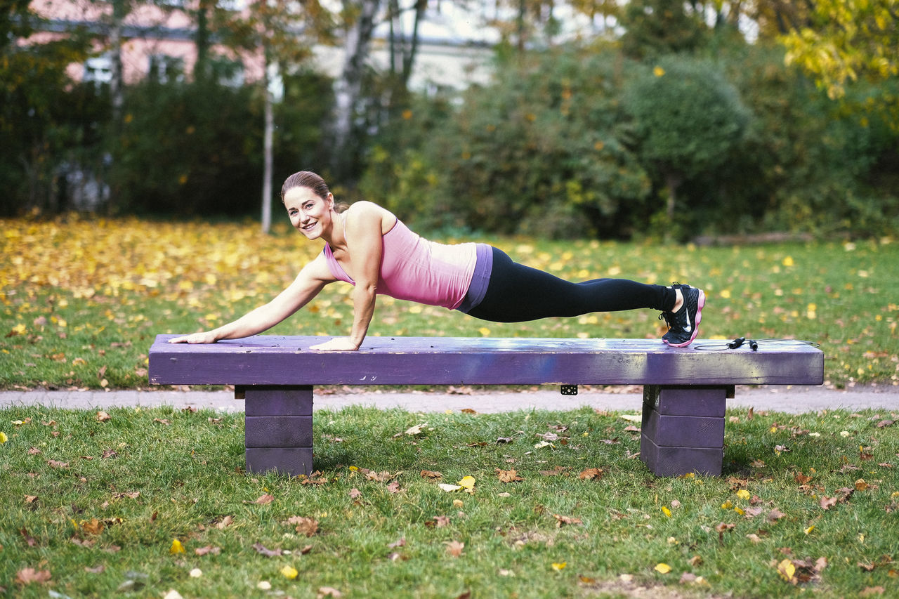 exercising, full length, sports clothing, healthy lifestyle, one person, vitality, day, lifestyles, young adult, outdoors, young women, wellbeing, smiling, leisure activity, park - man made space, only women, one woman only, women, happiness, grass, adult, one young woman only, nature, adults only, people
