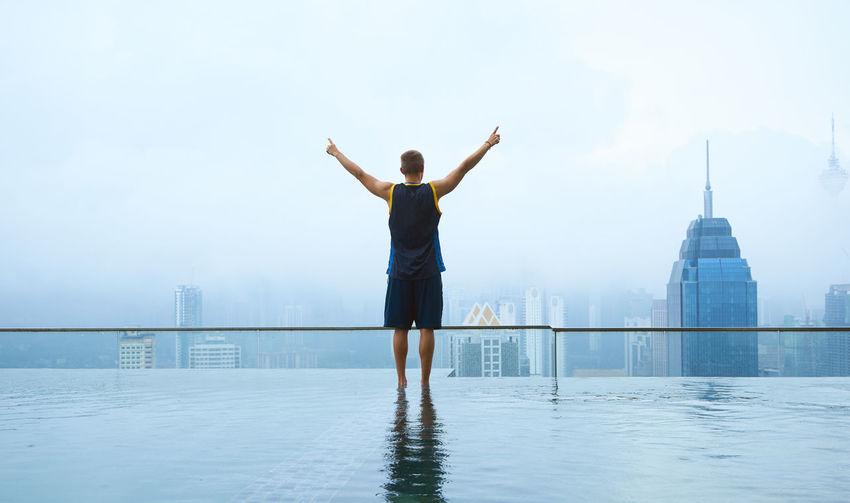 Man standing in infinity pool against sky in city