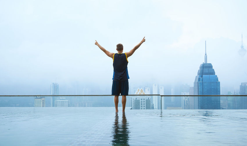 Rear view of man standing at swimming pool against sky