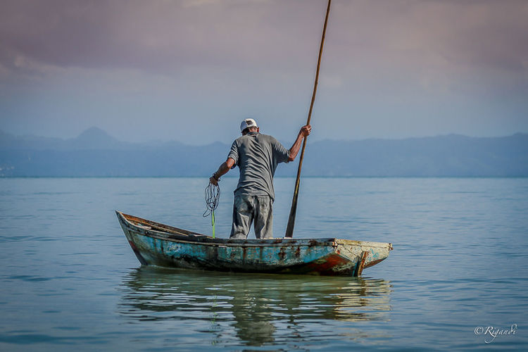early morning chores and fishing solo style Beauty In Nature Day Fisherman Fishing Fishing Net Full Length Men Mode Of Transport Mountain Nature Nautical Vessel Occupation One Man Only One Person Only Men Outdoors Real People Sailing Scenics Sea Sky Standing Transportation Water Wooden Raft