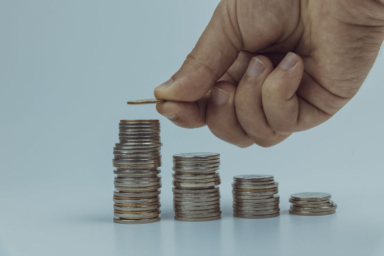 Savings or investment growth concept image with male hand stacking coin to top of other money coin stacks Coin Finance Human Hand Wealth Hand Human Body Part Stack Currency Savings Business Human Finger Finger Studio Shot Unrecognizable Person One Person Investment Body Part Large Group Of Objects Holding Diagram Making Money Economy Silver Colored Stacking Coin Stacks