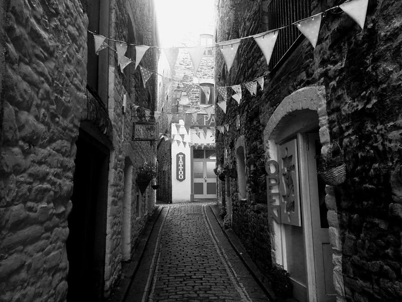 Architecture Built Structure Building Exterior The Way Forward Alley Day No People Path Tattoo Shop Bunting Blackandwhite Blackandwhite Photography Streetphotography Street Alley Photography EyeEmNewHere Plymouth Cobblestone Cobblestone Streets Old Town Black And White Friday