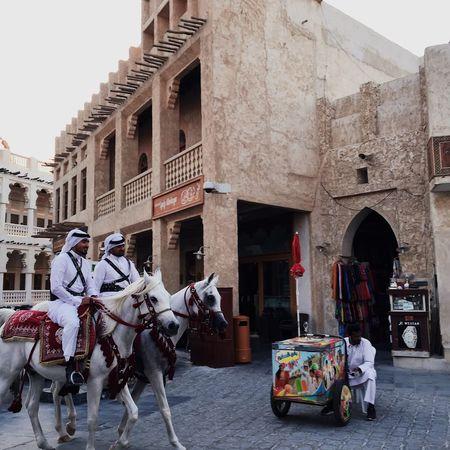 EyeEmNewHere Architecture Built Structure History Building Exterior Men Real People Day Travel Destinations Outdoors City People Travel Architecture Clear Sky City Pearl Doha Market Stall Middle East Adult Horse Horses