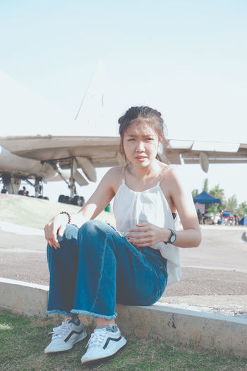 Full length of young woman sitting by airplane at airport