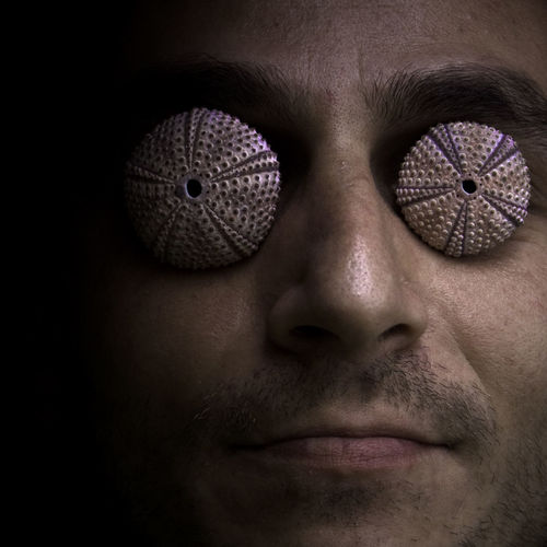 Close-up of man covering eyes with sea urchins