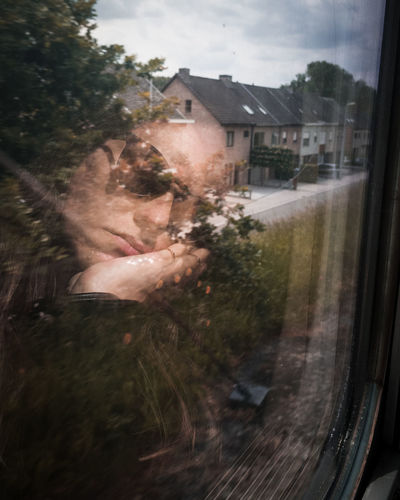 Portrait of woman seen through glass window of house