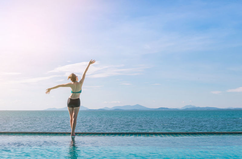 Rear View Of Woman With Arms Raised Standing At Infinity Pool By Sea