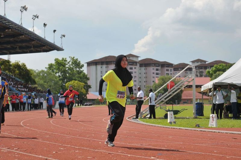 Woman running on sports track during competition