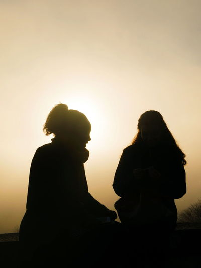 Silhouette couple sitting against clear sky during sunset