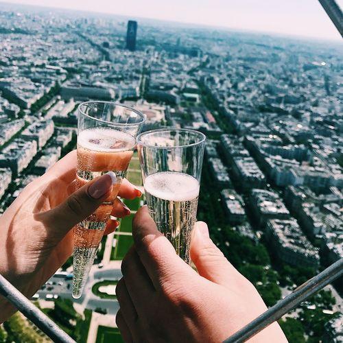 Cropped hands toasting champagne flutes against cityscape