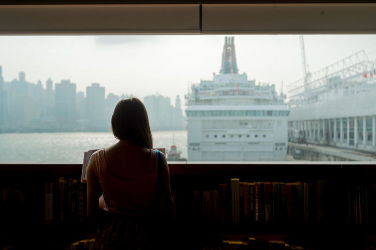 Rear view of woman standing in library against sky
