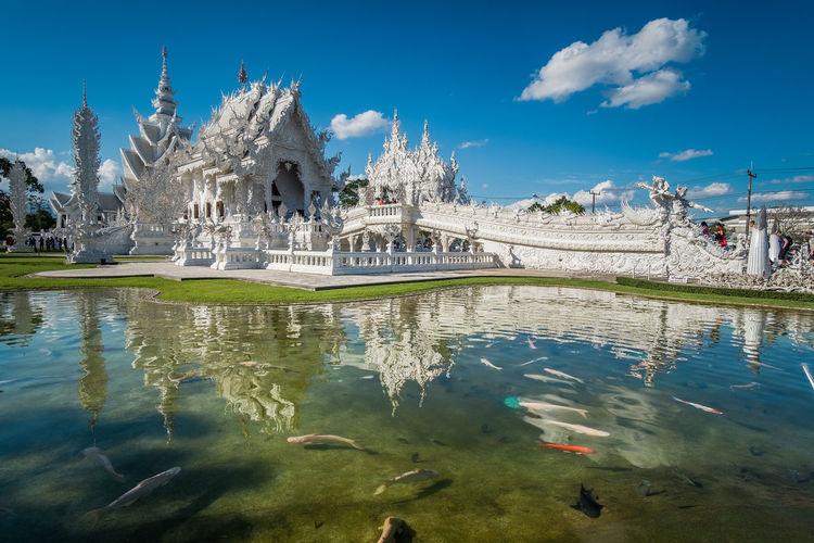 Pond by wat rong khun against sky