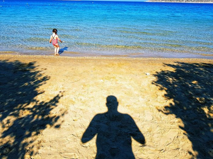 Rear view of girl standing by shadow at beach