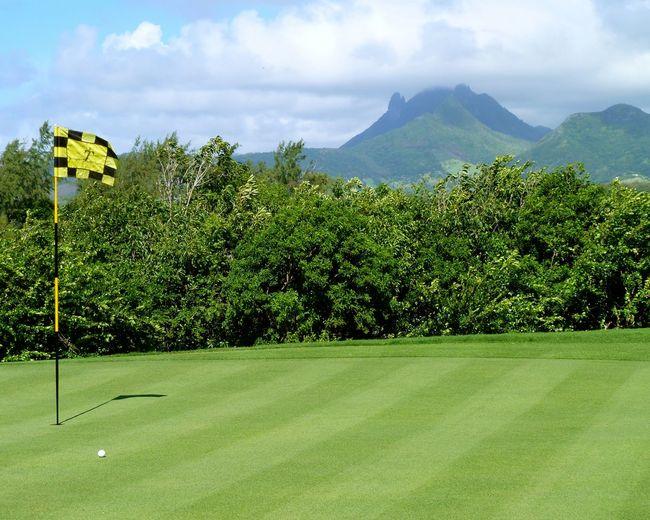 Flag and golf course against sky