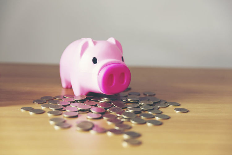 Close-up of coins with piggy bank on wooden table