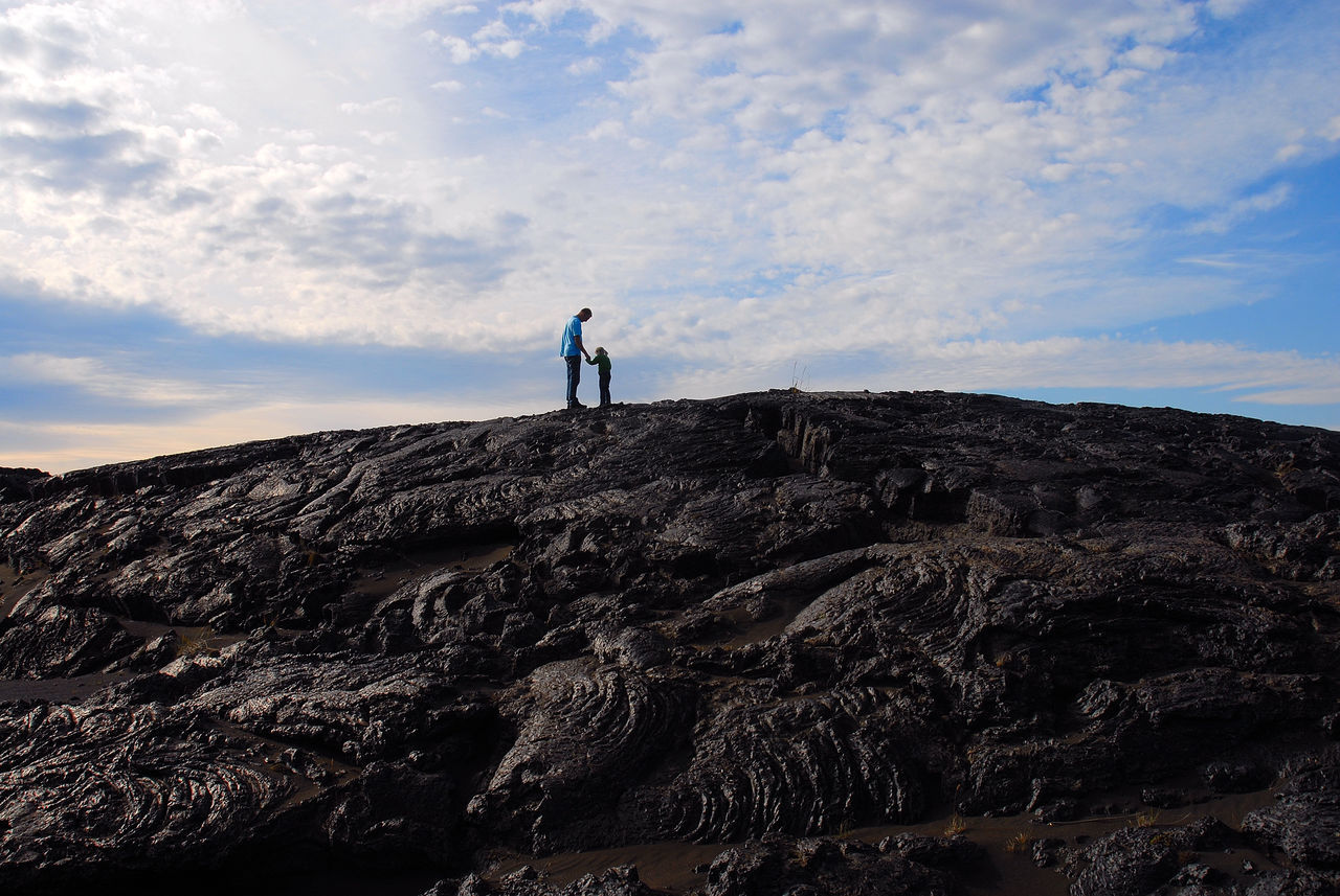 Low angle view of child and father standing on mountain against cloudy sky