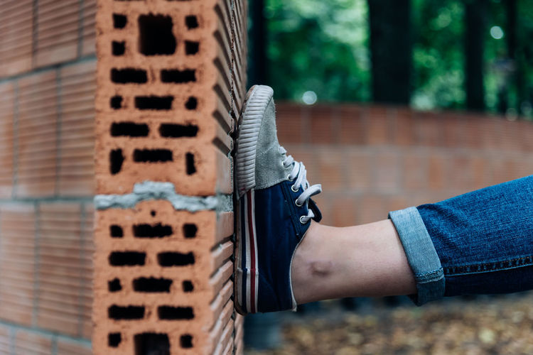 Close-up of leg on curved brick wall
