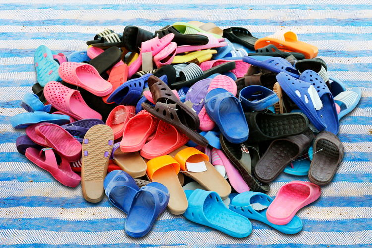 Piles of shoes sold in various color combinations rural land market, sandals, casual shoes, old. Abundance Beach Choice Day Diving Equipment Land Large Group Of Objects Multi Colored Nature No People Outdoors Sandal Sea Shoe Slipper  Still Life Underwater Variation Water