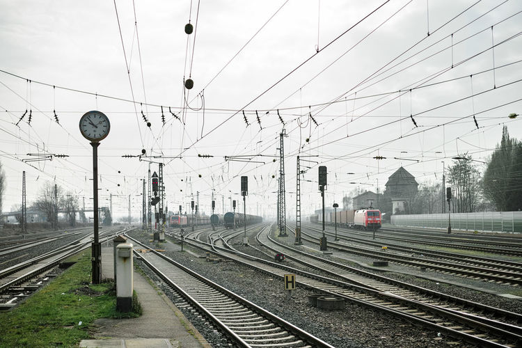 Railway Station Cable Day Diminishing Perspective Journey Mode Of Transport No People Outdoors Power Cable Power Line  Rail Transportation Railroad Station Railroad Station Platform Railroad Track Railway Track Sky The Way Forward Train Train - Vehicle Transportation Vanishing Point