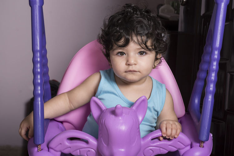 Portrait of a little baby girl on unicorn swing, equipped at home for kids Childhood Child Indoors  Portrait One Person Front View Finance Investment Piggy Bank Pink Color Real People Innocence Curly Hair Savings Cute Looking At Camera Lifestyles Purple Hairstyle
