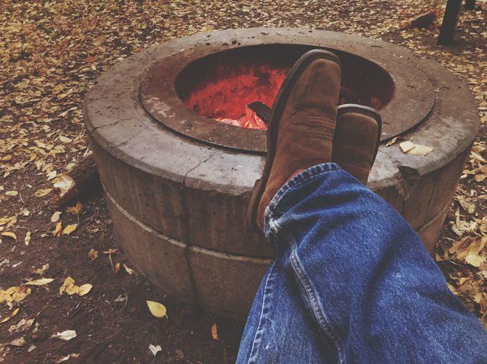 Low section of man with feet up on fire pit