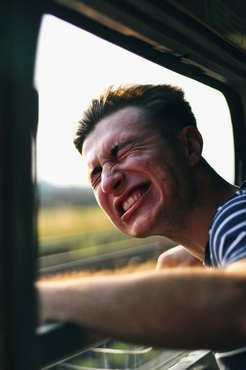 Smiling young man making a face while peeking out from train window