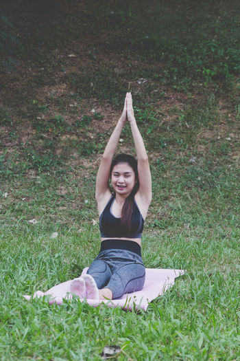 Woman practicing yoga while sitting on grass outdoors