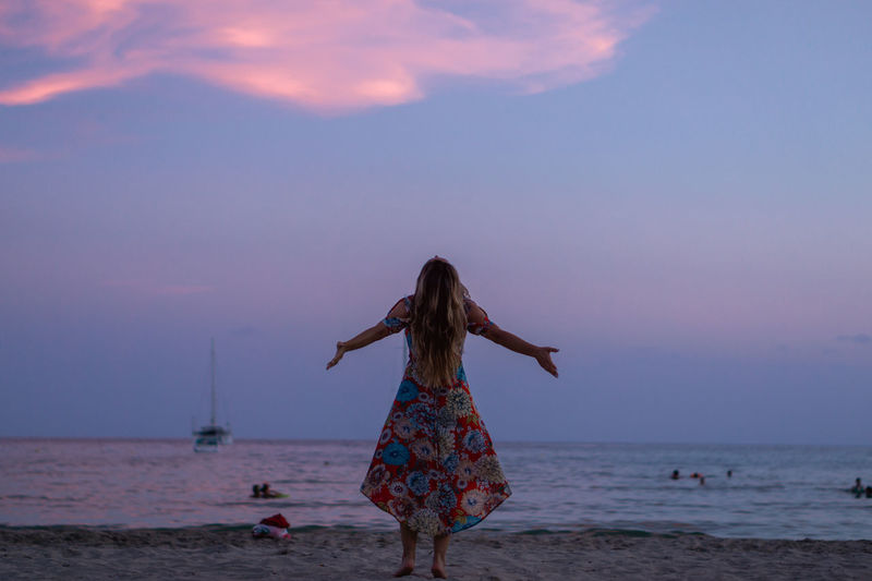 Rear view of woman on beach against sky during sunset