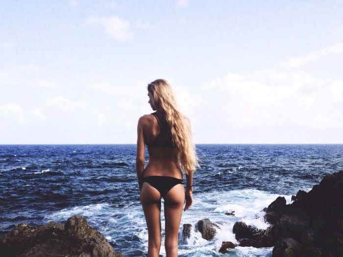 Rear View Of Young Woman Wearing Bikini And Standing Against Sea