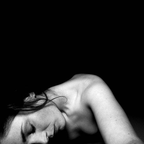 Shirtless young woman lying against black background