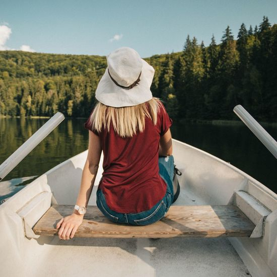 Rear View Of Woman Sitting On Boat Against Lake